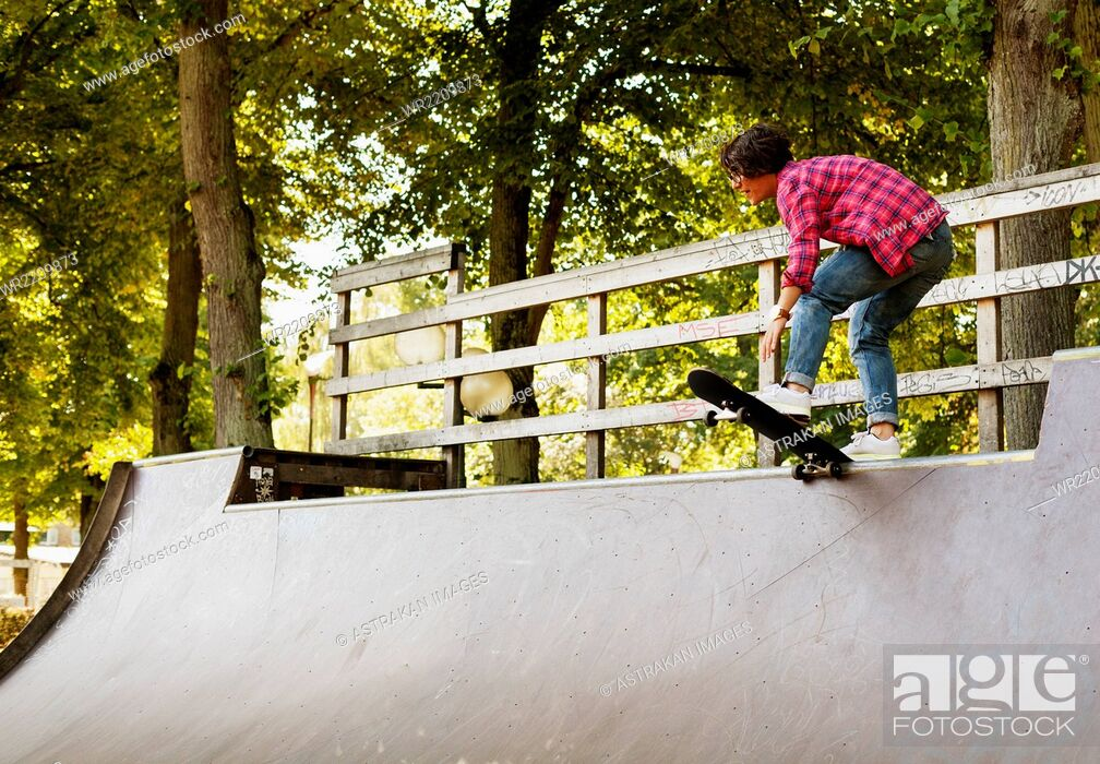 Stock Photo: Teenage girl standing with skateboard on ramp at park.