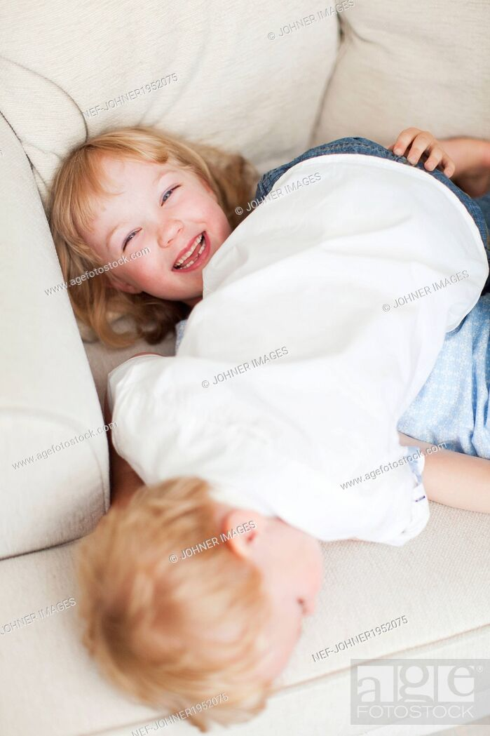 Stock Photo: Brother and sister playing on sofa, Sweden.