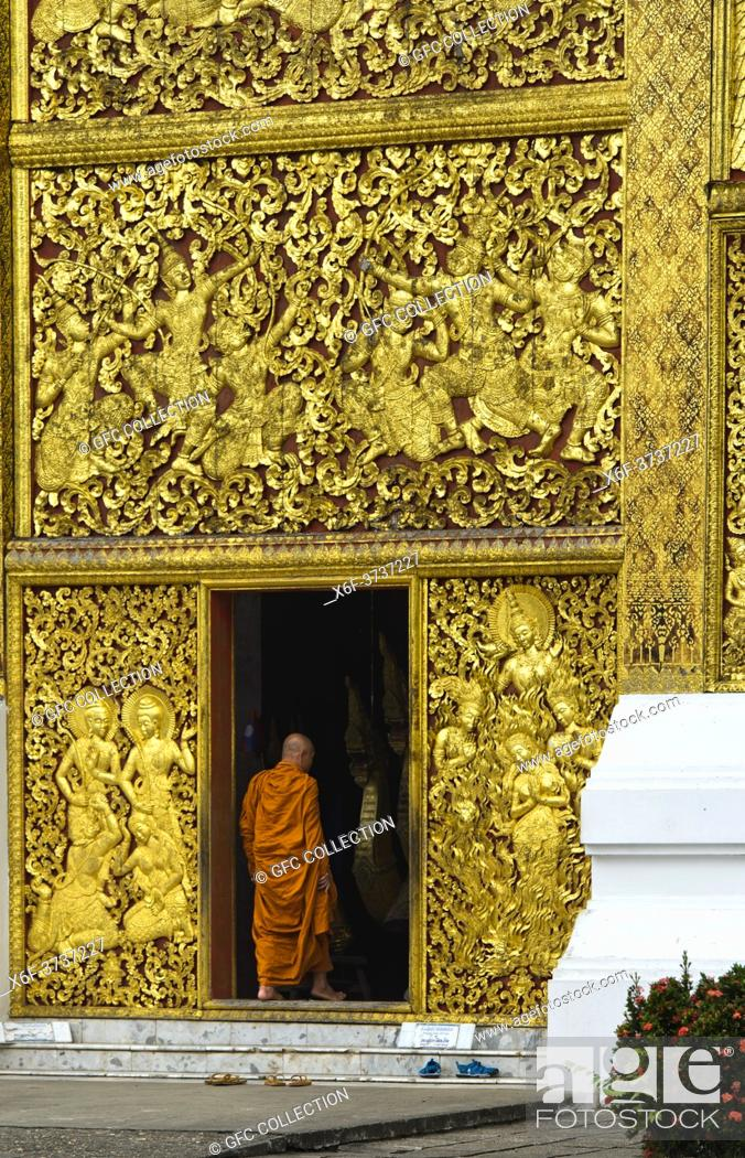 Stock Photo: Gilded teak wood panels depicting the Lao version of Ramayana story (Lao Pha Lak Pha Lam) at the entrance to the Royal Funerary Carriage house.