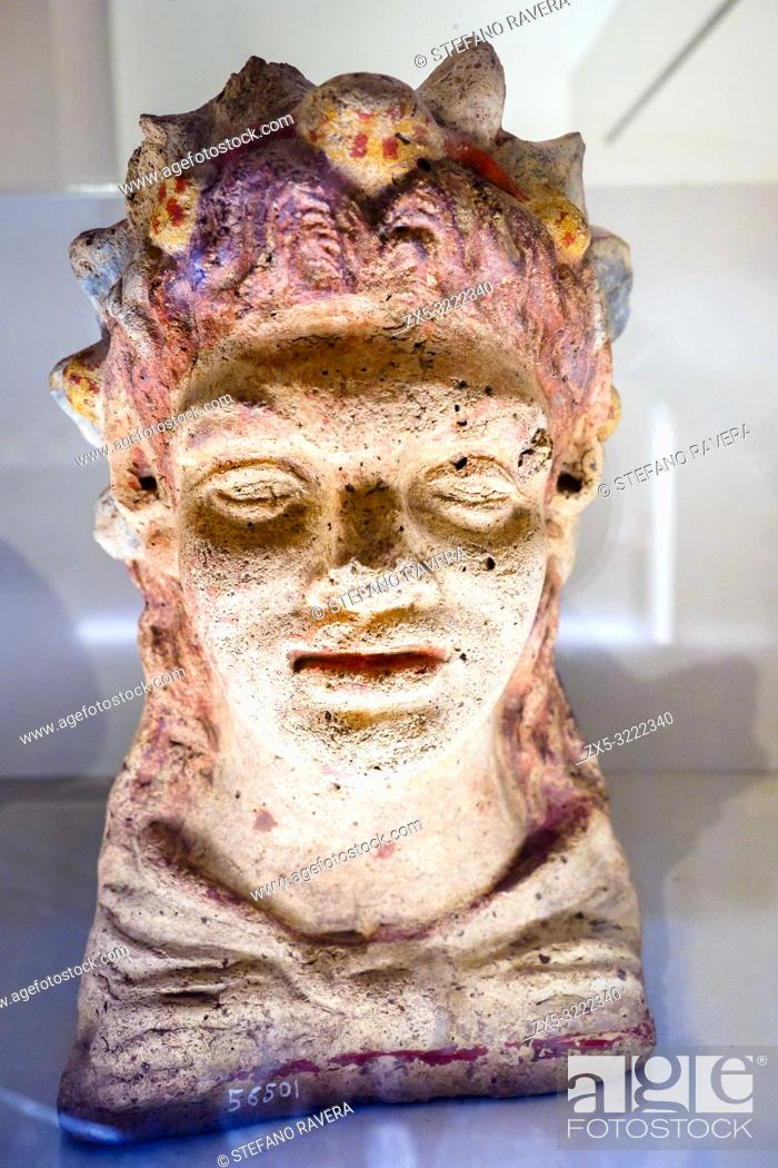 Stock Photo: Terracotta antefix in head of a smiling young satyr with a wreath of berries and leaves from the sanctuary of Hercules in the locality of sant'Antonio -.