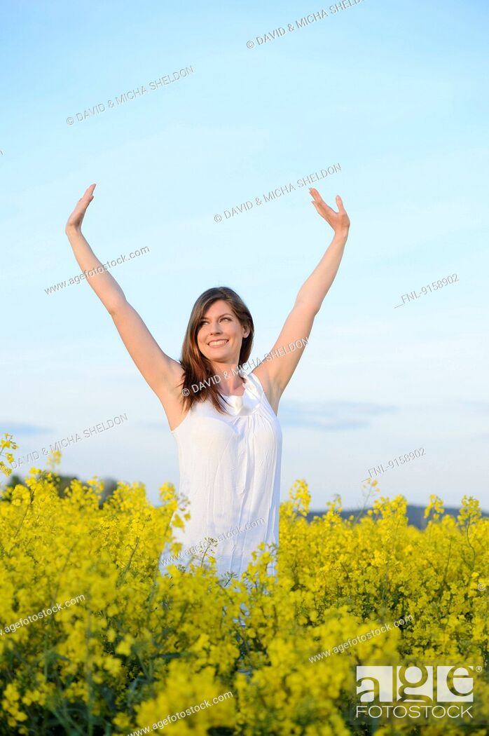 Stock Photo: Young woman in rape field, Bavaria, Germany, Europe.
