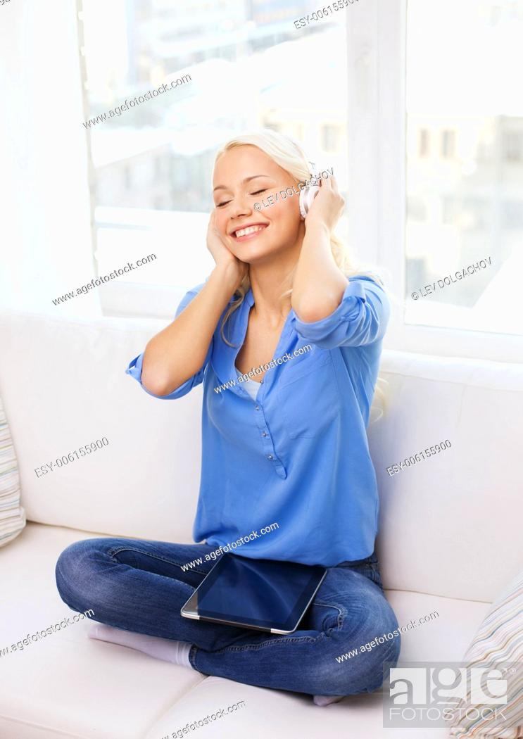 Stock Photo: home, music, technology and internet concept - smiling woman sitting on the couch with tablet pc computer and headphones at home.