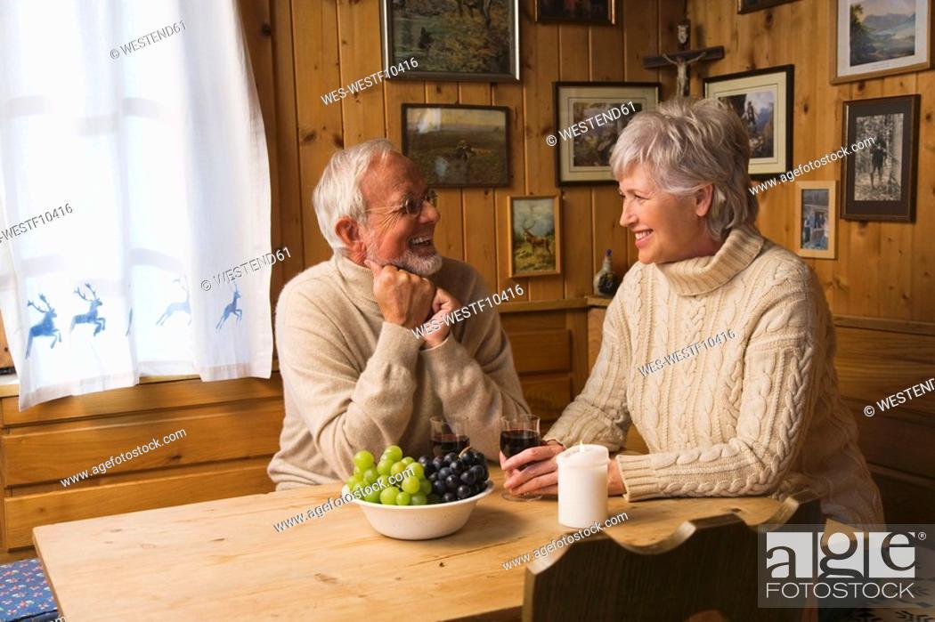 Stock Photo: Senior couple sitting at table, smiling.