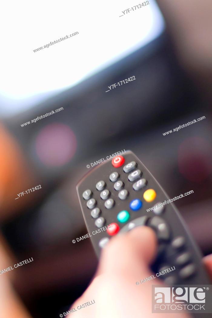 Stock Photo: Closeup on a hand changing channels on TV set with a infrared remote.