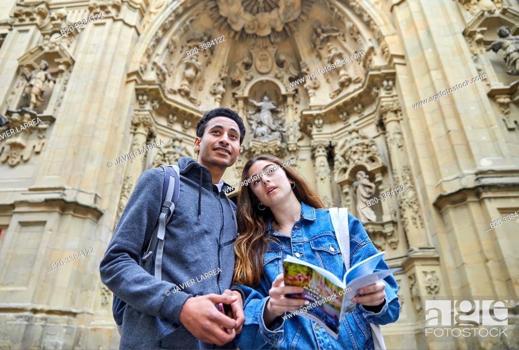 Stock Photo: Couple of tourists visiting the city, Multiracial young couple, Basilica de Nuestra Señora del Coro, Parroquia de Santa María, Donostia, San Sebastian, Gipuzkoa.