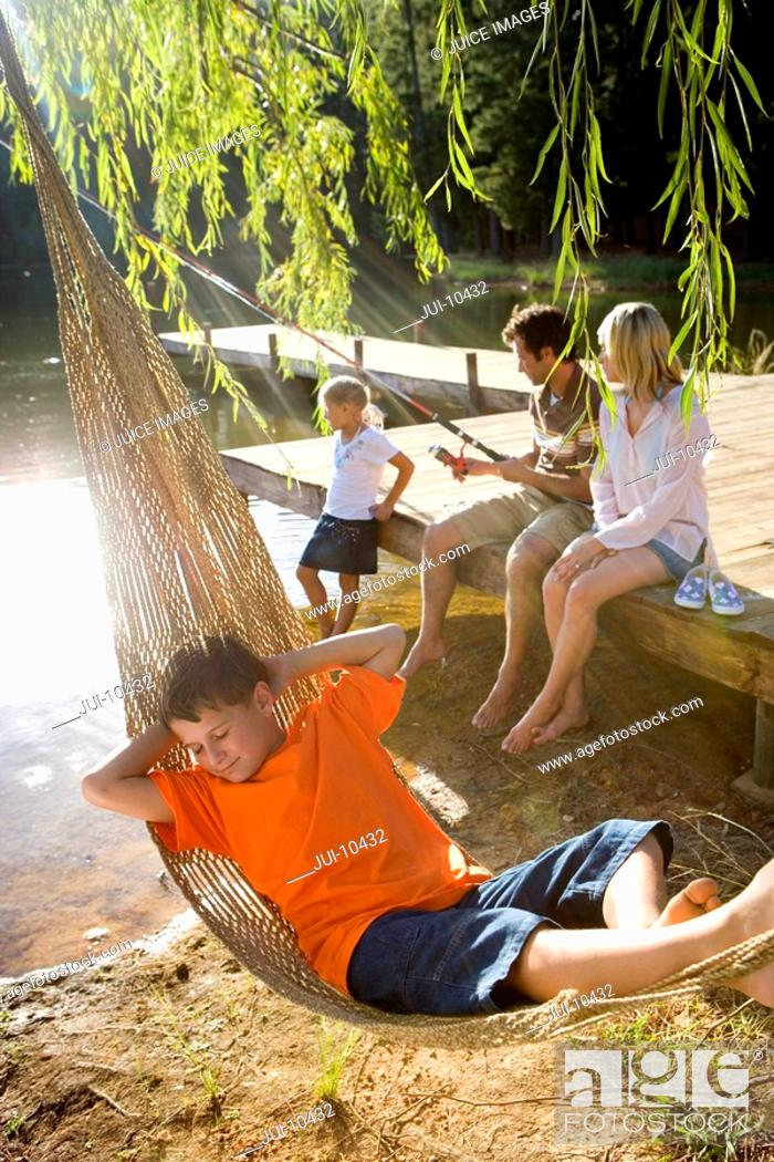 Stock Photo: Boy 6-8 in hammock by family fishing from jetty in background, elevated view lens flare.
