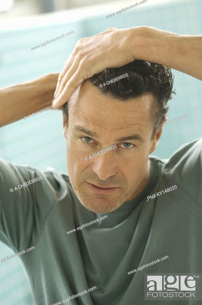 Stock Photo: Portrait of a man doing his hair.