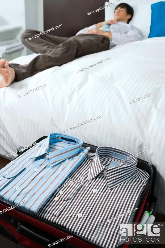 Stock Photo: Shirts in a suitcase and a businessman sleeping on the bed.