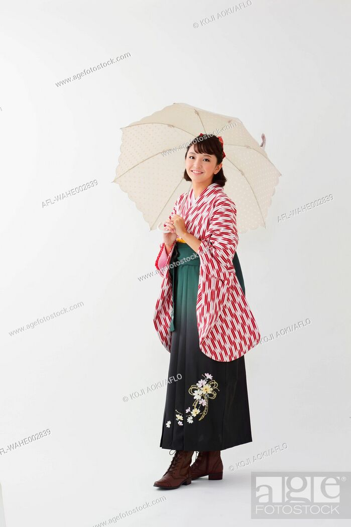 Stock Photo: Young Japanese girl in a kimono against white background.