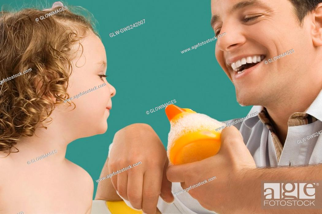 Stock Photo: Close-up of a mid adult man looking at his daughter and smiling.