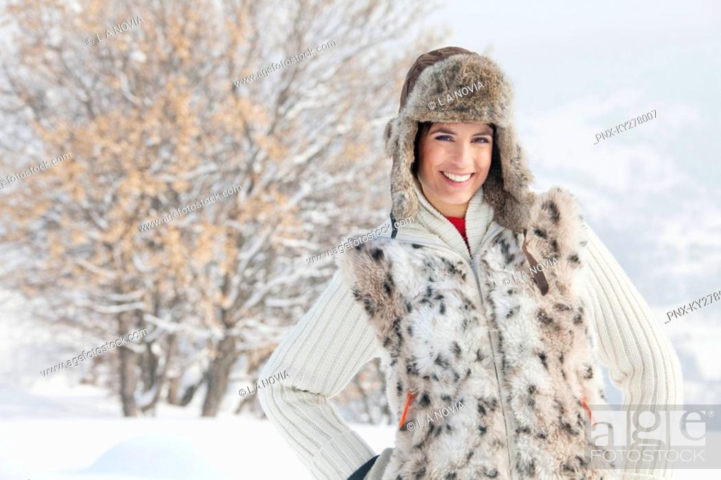Stock Photo: Young woman in winter clothes smiling at camera.