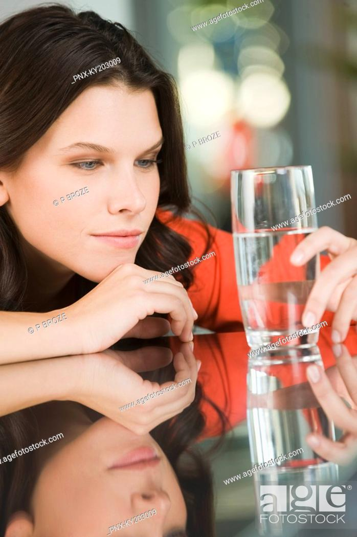 Stock Photo: Woman looking at a glass of water.