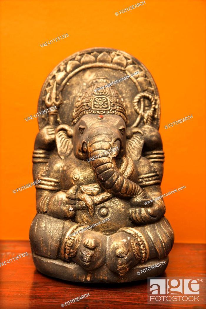 Stock Photo: Statue of Hindu elephant Ganesha against orange wall.