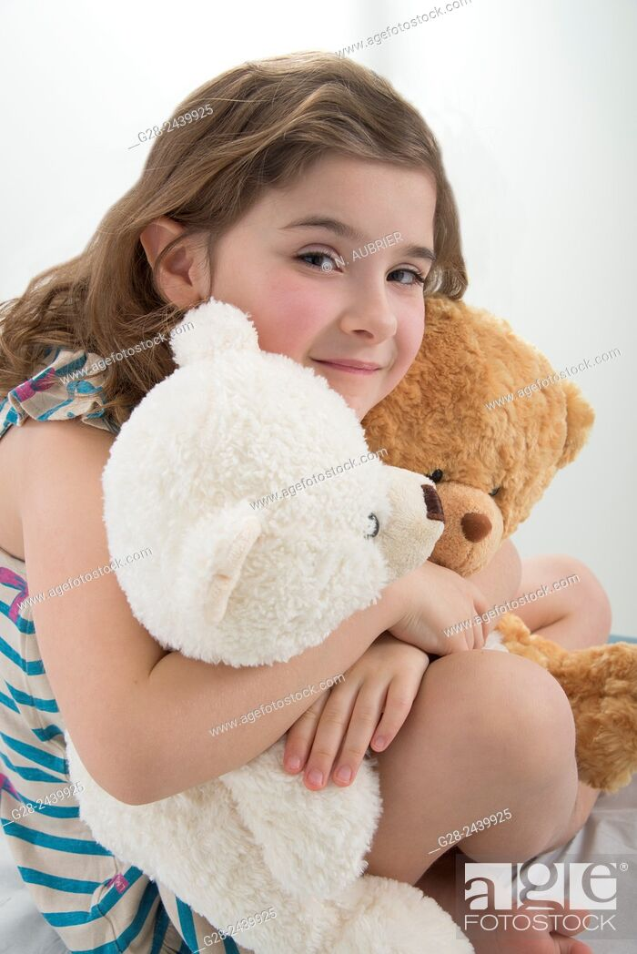 Stock Photo: Little girl holding two teddy bears and smiling.