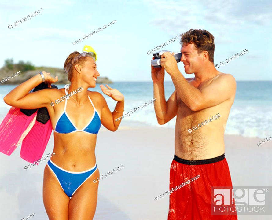 Stock Photo: Close-up of a young man taking a photograph of a young woman holding flippers, Bermuda.