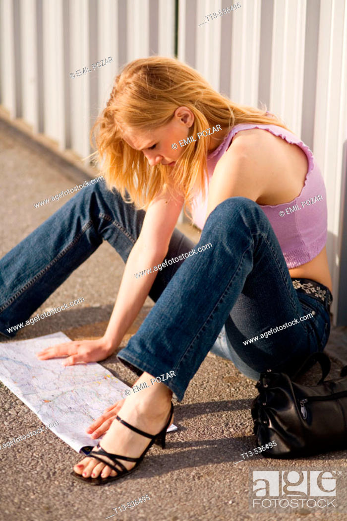 Stock Photo: Young blonde woman is reading a road map between her legs while sitting by the wall.