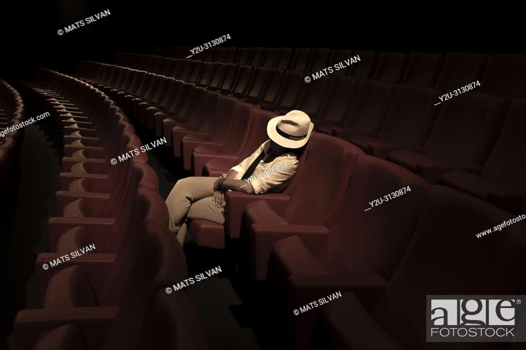 Stock Photo: Woman with Hat Sleeping Alone in Movie Theater.