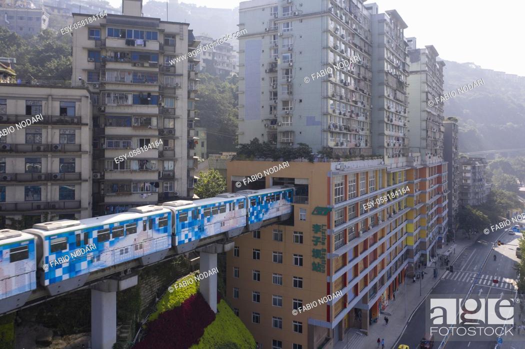 Stock Photo: Aerial view of subway train at Liziba station in Chongqing, China, passing through building.