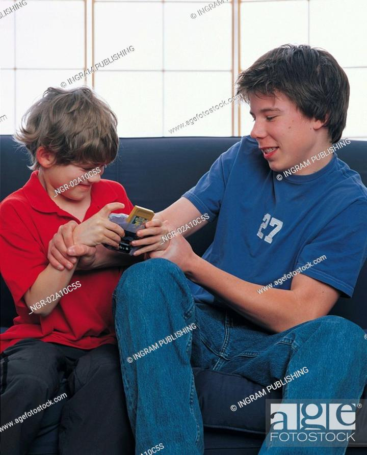 Stock Photo: two boys fighting over a video game.
