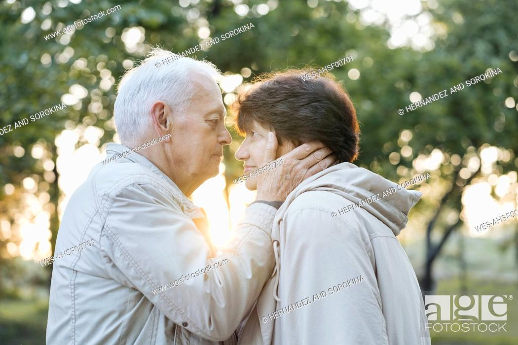 Stock Photo: Profile of senior couple in love at sunset.