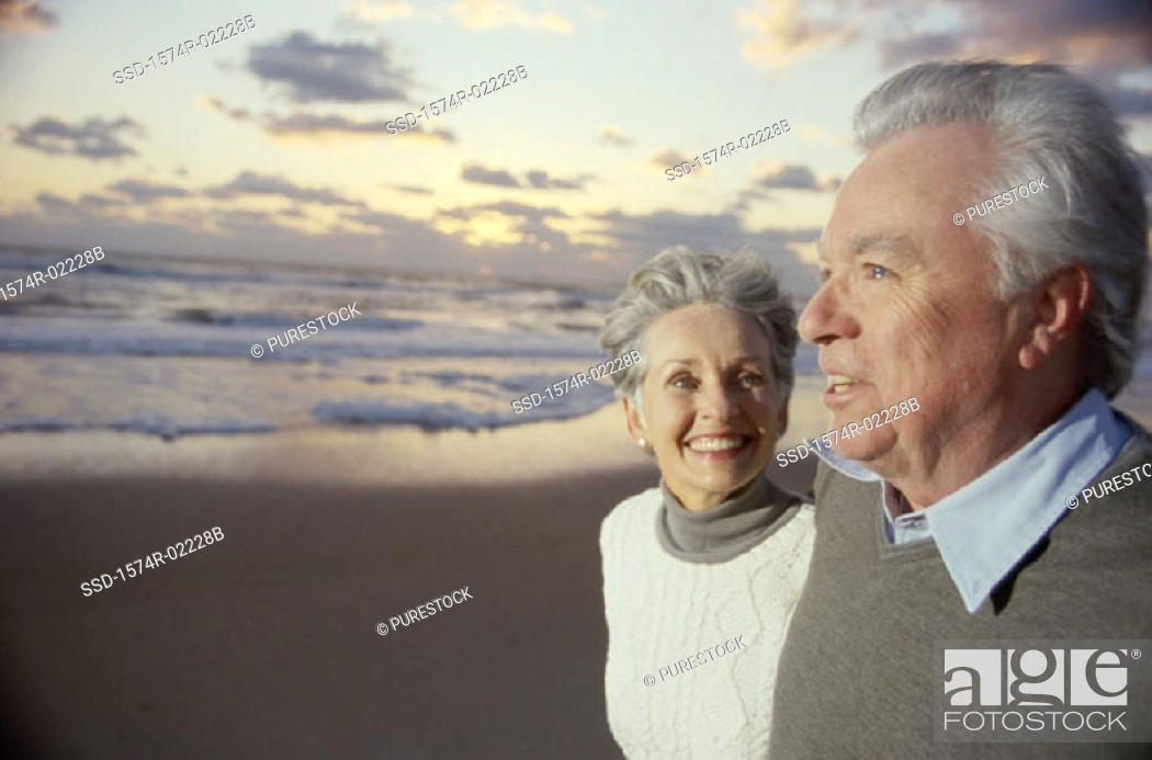 Stock Photo: Side profile of a senior couple standing on the beach.