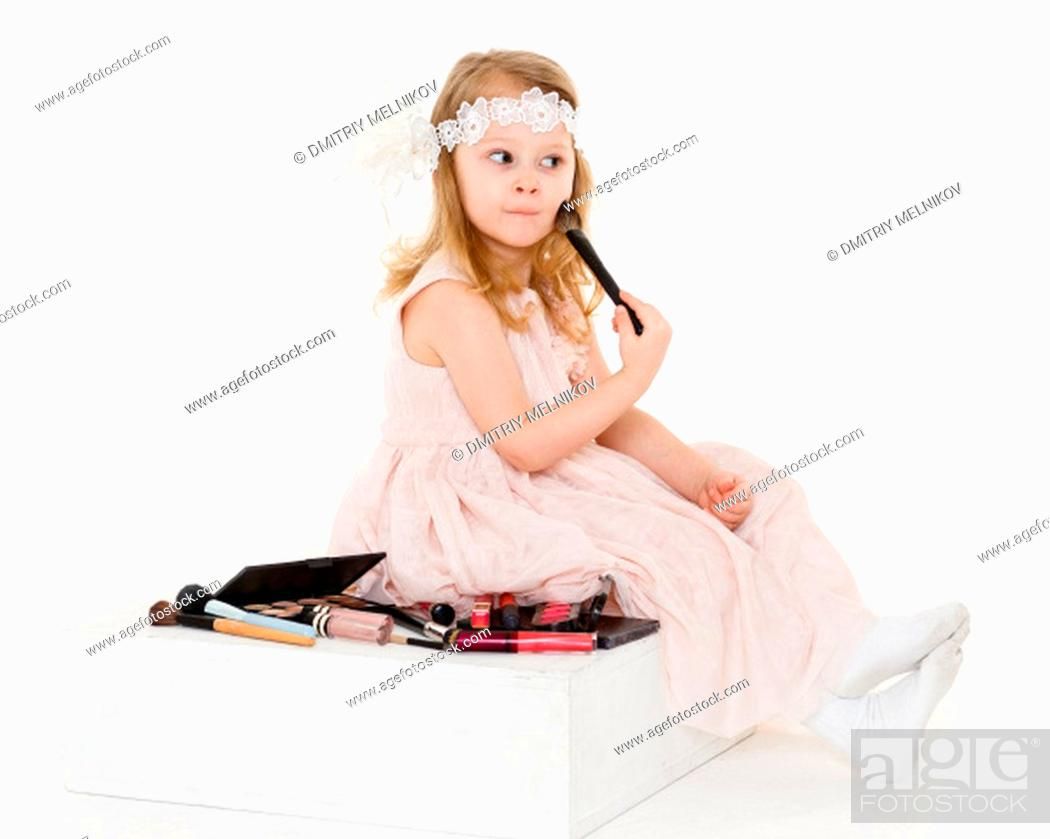 Stock Photo: Pretty little girl playing with cosmetics on a white background. 3 year old.