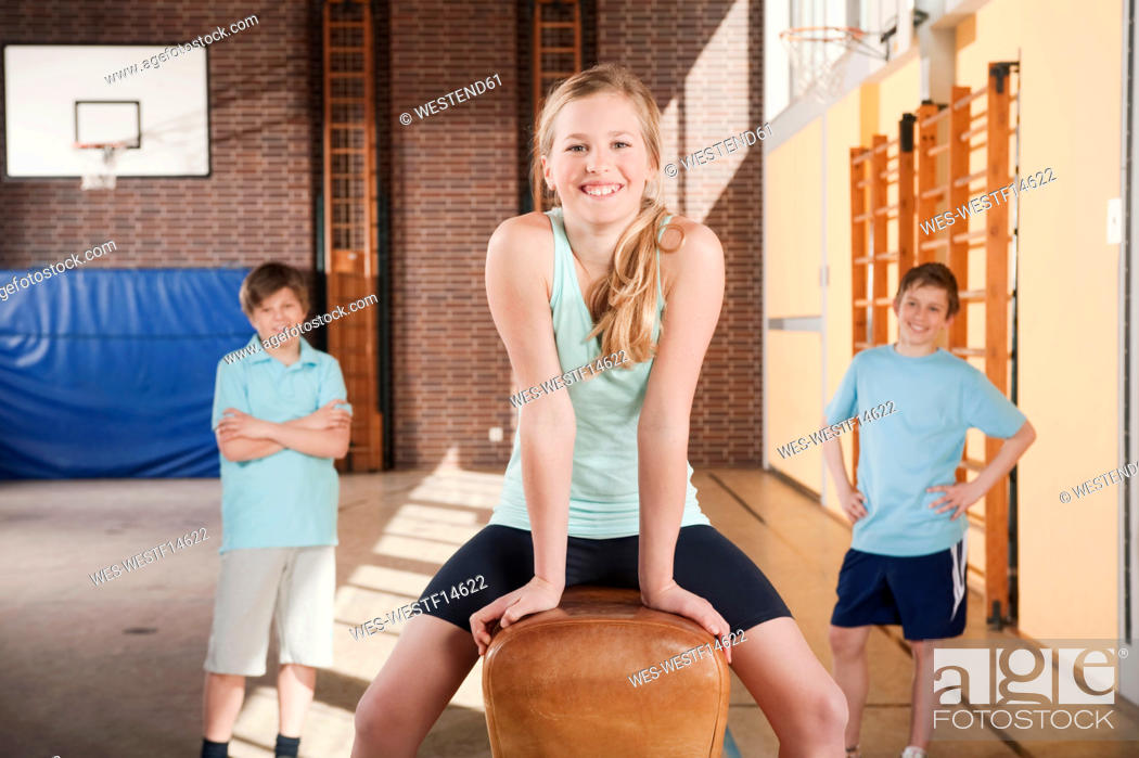 Stock Photo: Germany, Emmering, Girl 12-13 smiling with boys standing in background.