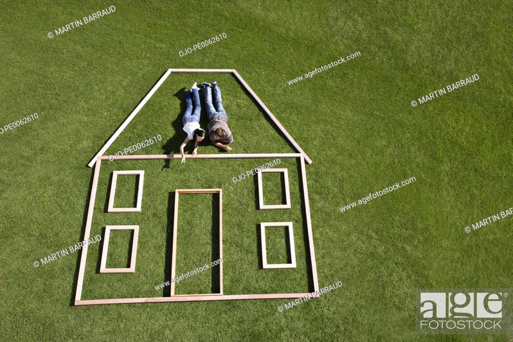 Stock Photo: Couple laying inside house outline.