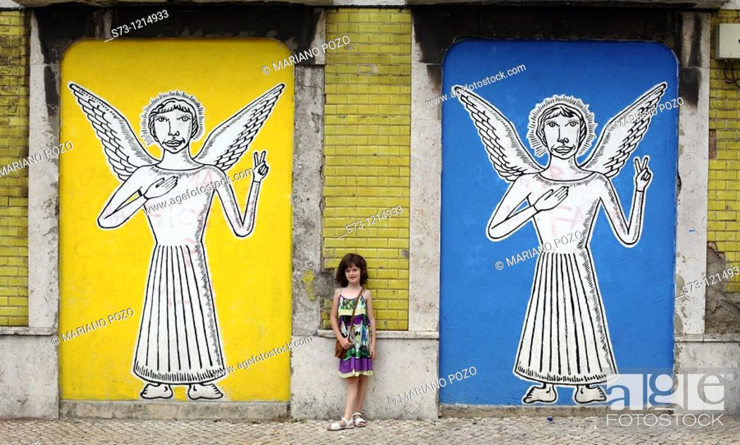 Stock Photo: Girl near a wall painting with angels in Lisbon streets, Portugal, Europe.
