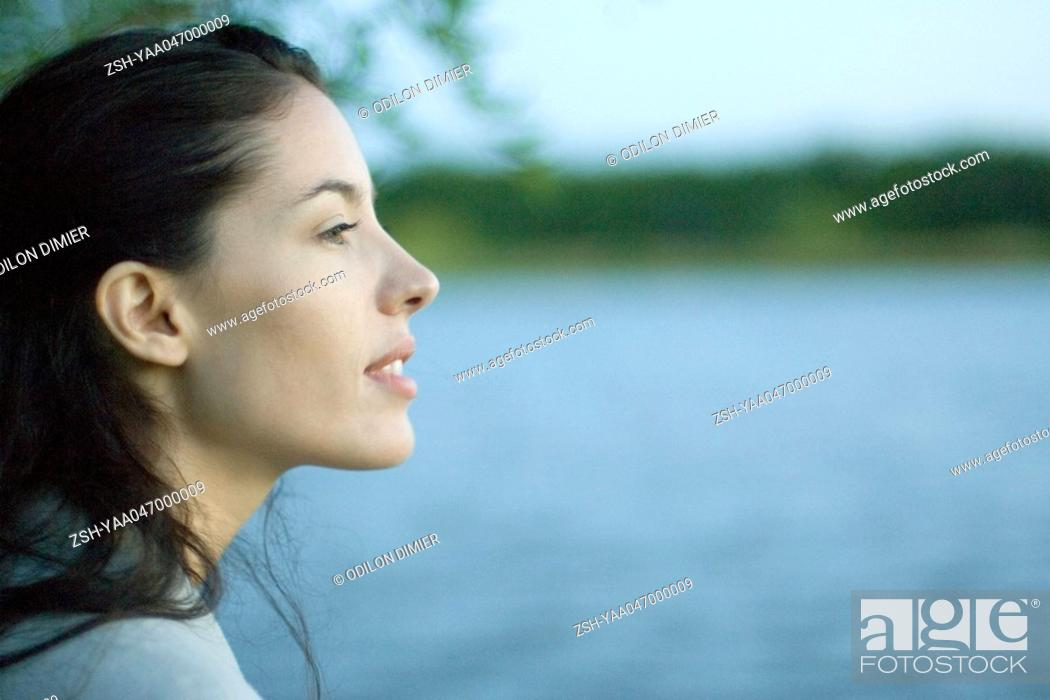 Stock Photo: Woman's profile, lack in background.