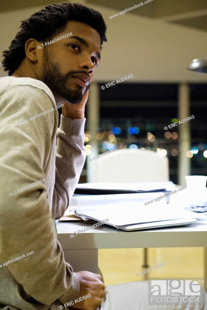 Stock Photo: Man sitting at desk in office at night, looking away in thought.