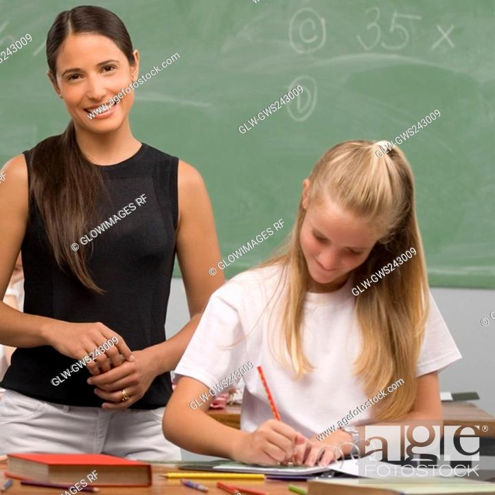 Stock Photo: Schoolgirl writing on a textbook with her female teacher standing behind her and smiling.