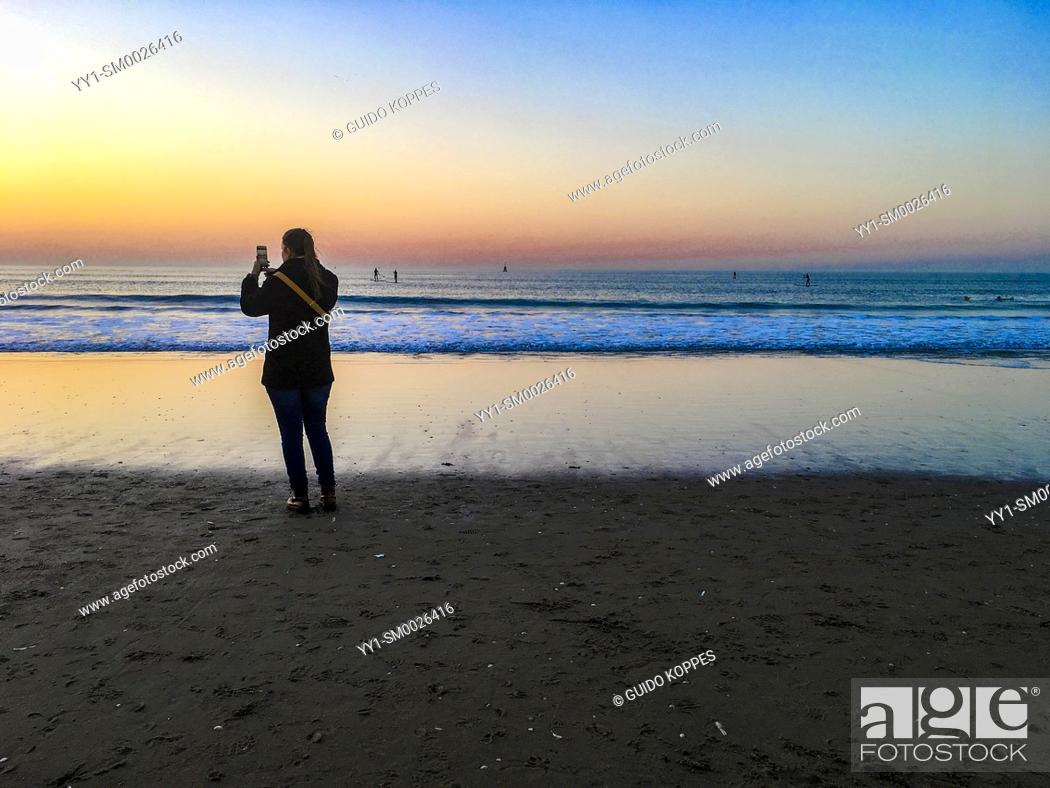 Imagen: The Hague, Scheveningen, Netherlands. Young adult woman enjoying and capturing a beautifull sunset on the North Sea Beach during a warm.