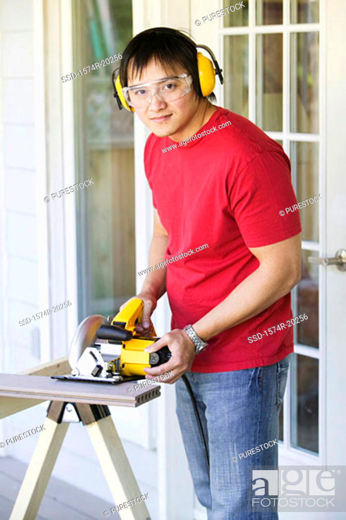Stock Photo: Portrait of a young man cutting a plank with an electric saw.