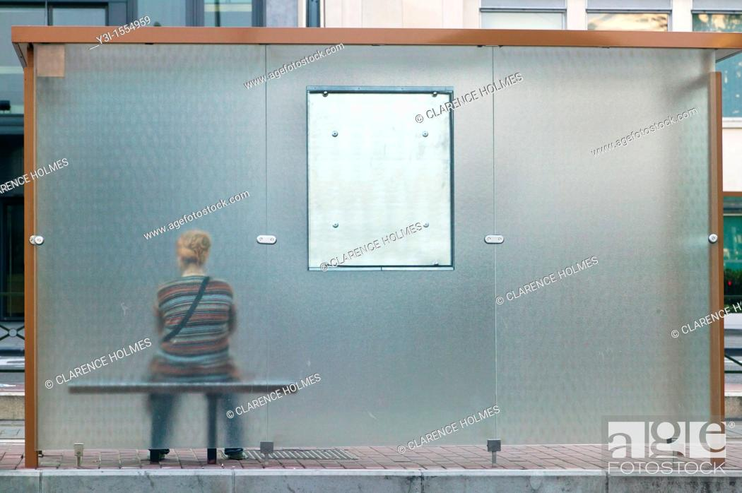 Stock Photo: A woman waits at a bus stop in Brussels, Belgium.