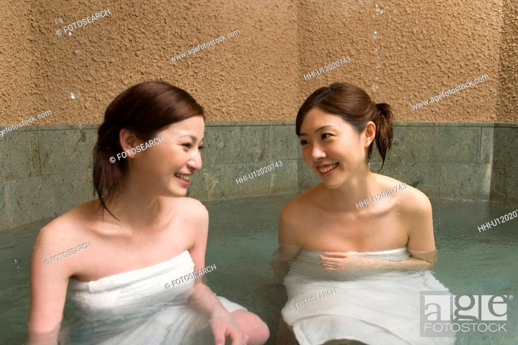Stock Photo: Two women in hot tub, smiling, front view, Japan.