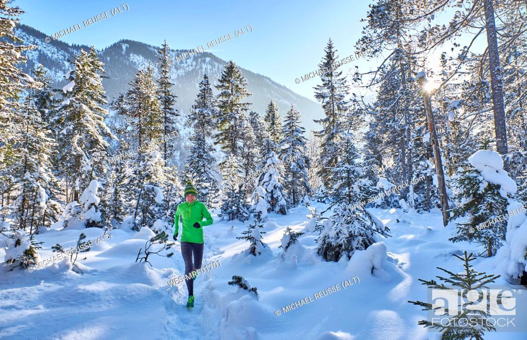 Stock Photo: Germany, Bavaria, Isar valley, Vorderriss, woman jogging in winter forest.