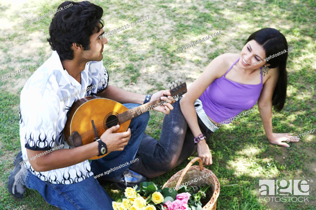 Stock Photo: High angle view of a young man playing the mandolin with a young woman looking at him.