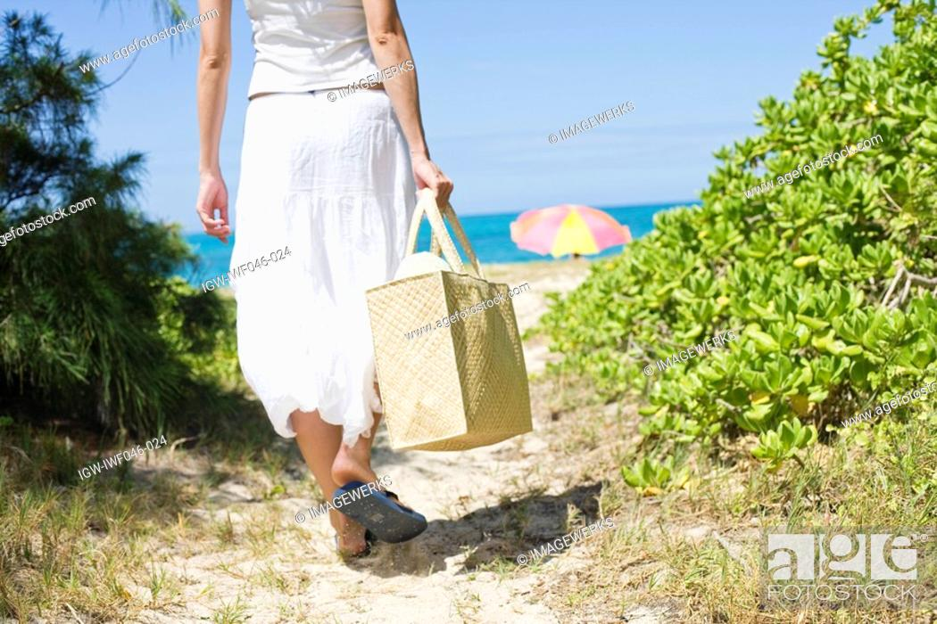 Stock Photo: Rear view of a woman walking towards beach.
