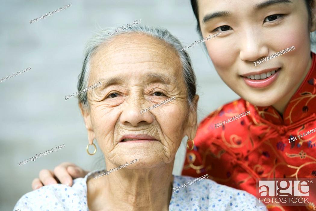 Stock Photo: Young woman wearing traditional Chinese clothing posing with elderly grandmother, portrait.