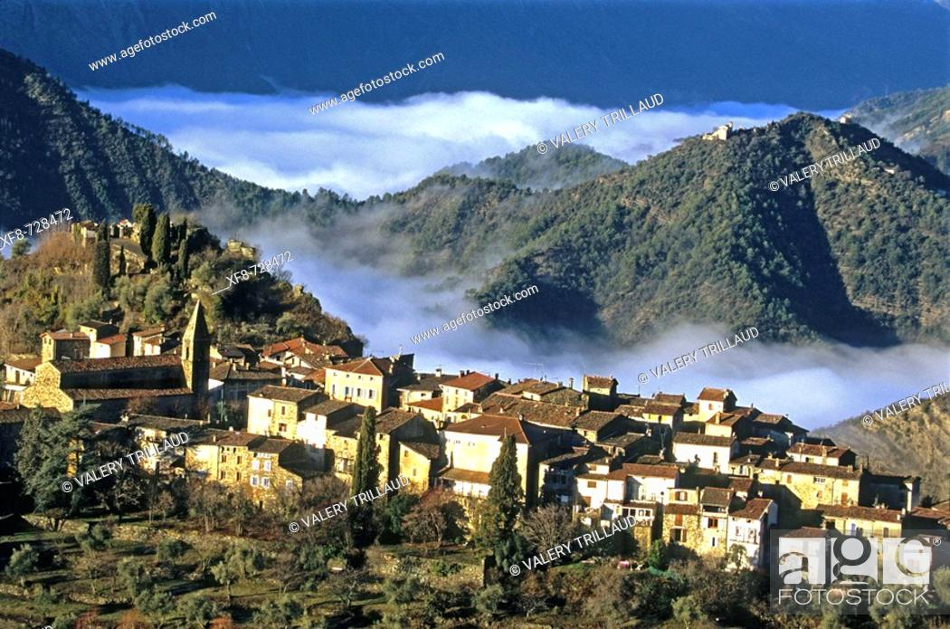 Stock Photo: The little perched village of La Tour early in the morning and the foggy Tinee valley. Alpes Maritimes, France.