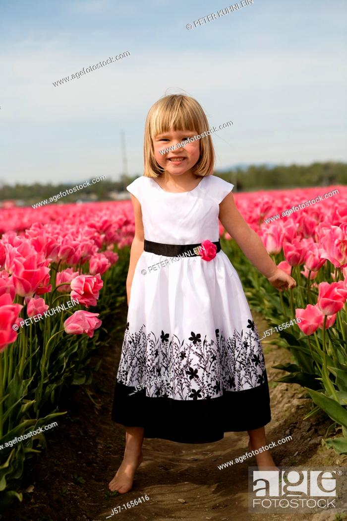 Stock Photo: 4 year old girl in black and white dress playing and smiling in a tulip fields in Skagit Valley, Washington, USA.