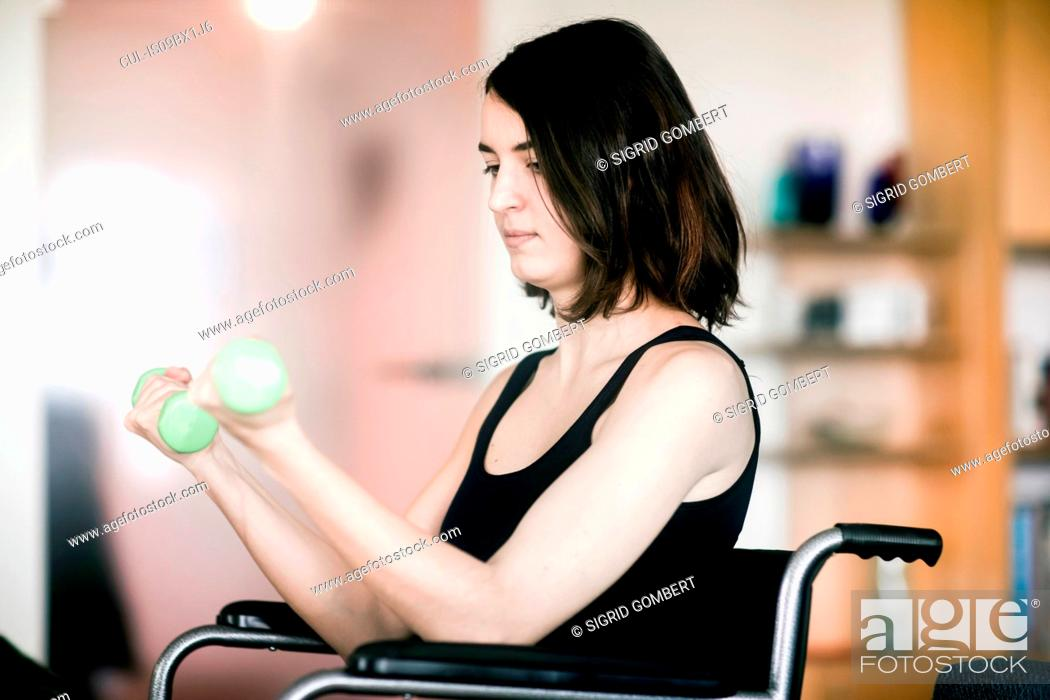 Stock Photo: Woman in wheelchair using weights at home.
