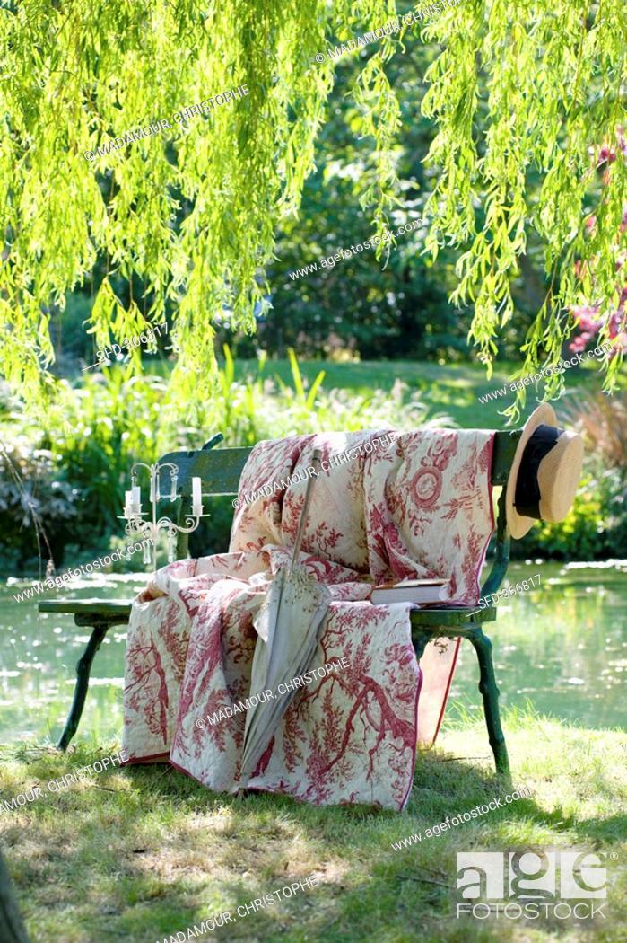 Stock Photo: Romantic garden seat by pond.