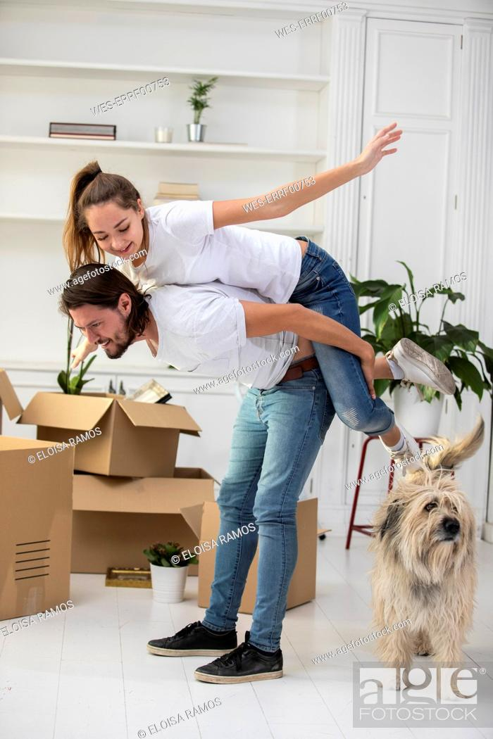 Stock Photo: Happy couple with dog and cardboard boxes in new home.