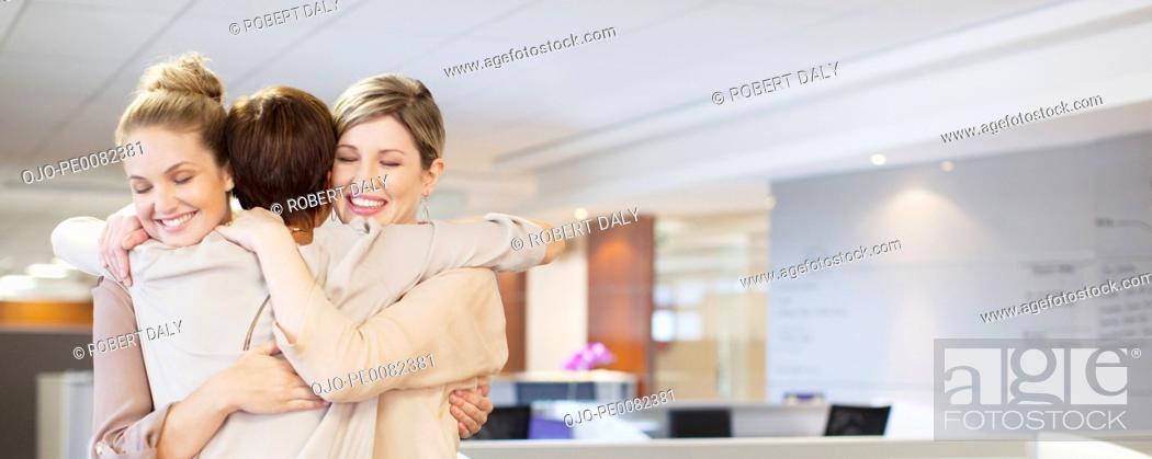 Stock Photo: Businesswomen hugging in office.