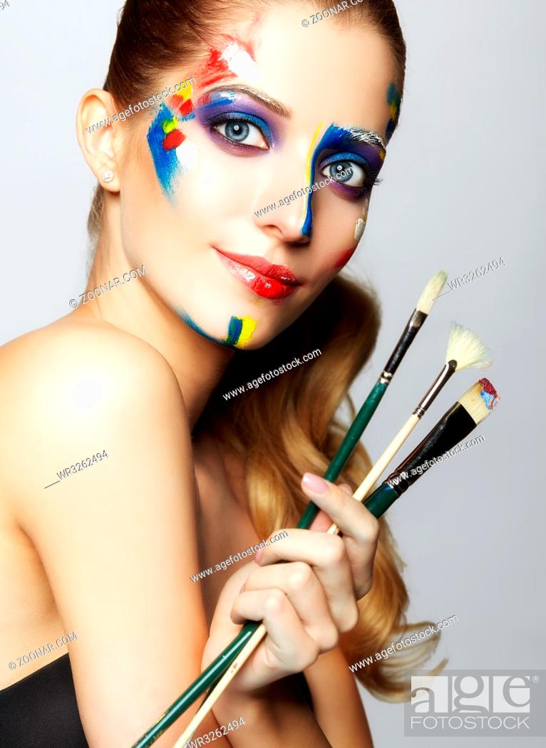 Photo de stock: Young woman painter with paint brush in hand and acrylic paint on face.