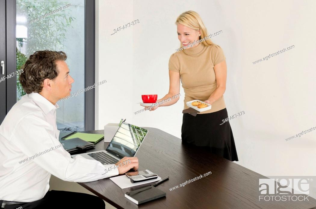 Stock Photo: Woman serving coffee and pastry for businessman at desk.