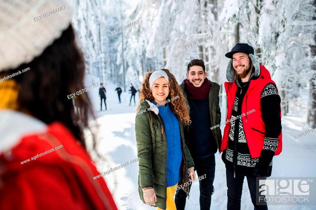 Stock Photo: A group of young cheerful friends on a walk outdoors in snow in winter, talking.