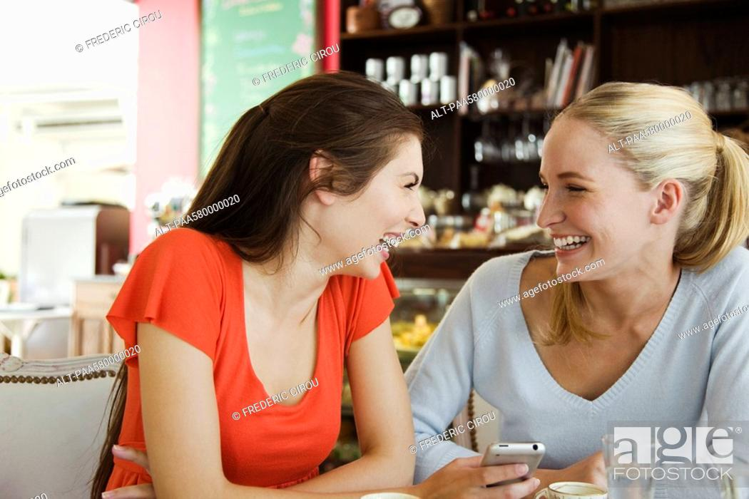 Stock Photo: Female friends together at cafe, laughing.